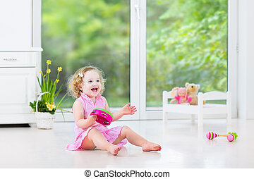 Cute curly laughing toddler girl in a pink dress playing tambourine and maracas in a sunny room with a big garden view window with a toy bed and spring flowers next to her, white modern interior home