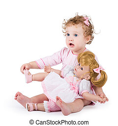 Cute toddler girl playing with her first doll