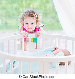 Cute toddler girl playing with her newborn baby brother in a bed