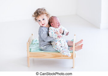 Cute toddler girl playing with her newborn baby brother in a woo