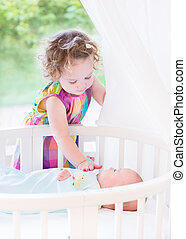 Cute toddler girl playing with her newborn baby brother laying i