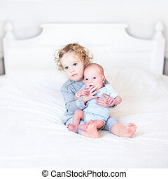 Cute toddler girl playing with her newborn baby brother