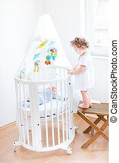 Cute toddler girl standing on a chair and watching her newborn b