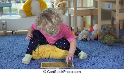 Cute toddler girl use tablet pc sitting on blue carpet....