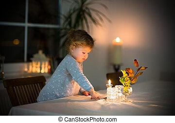 Cute toddler girl watching burning candles in a beautiful dark d