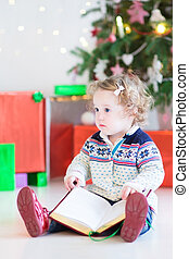 Cute toddler girl with curly hair reading a book under a beautif