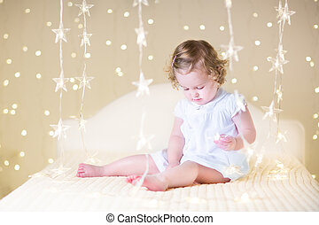 Cute toddler girl with curly hair wearing a white dress playing
