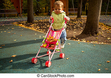 cute toddler kid carries yellow leaves in baby stroller in the autumn park.