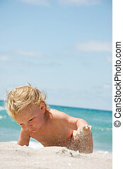 cute toddler playing in sand on beach