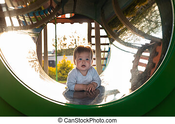 Cute toddler playing on the playground, crawls in a tube. Outdoors. Happy Children's Day