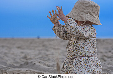 Cute toddler playing with sand on the beach