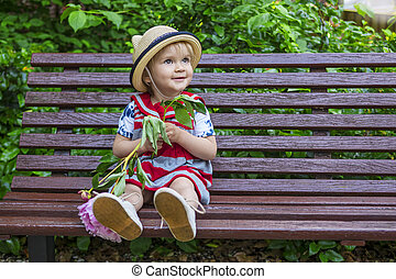 Cute toddler sitting on a bench with a flower