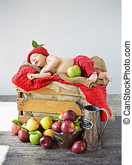 Cute toddler sleeping on a box of apples
