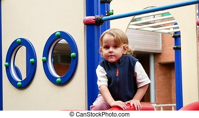 Cute toddler sliding down on playground