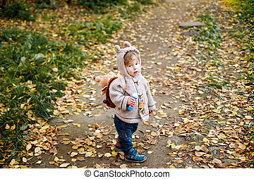 Cute toddler with animal ears hood walking in the park, full height, view from above