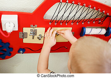 Cute toddlers playing with busy board at kindergarten