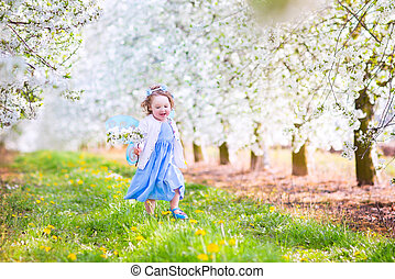 Cute toddlger girl in fairy costume playing in a blooming garden