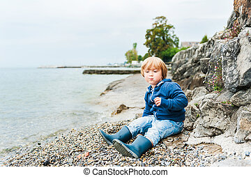 Cute toodler boy having fun outdoors, playing next to lake on a rainy day