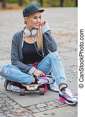 Cute trendy woman relaxing with her skate board