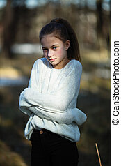 Cute twelve year old girl in the park posing for the camera.