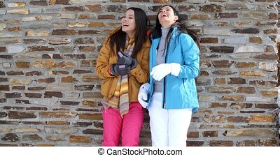 Cute twins in winter coats leaning on wall