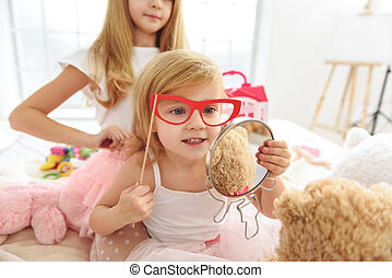 Cute two small girls entertaining in bedroom