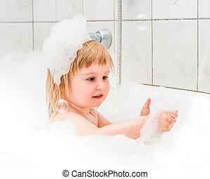 cute two year old baby bathes in a bath with foam closeup