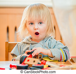 cute two-year old baby playing with constructor