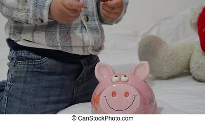 cute two years old baby boy playing with piggy bank and putting coins inside
