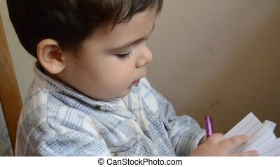 cute two years old baby boy taking notes like big man