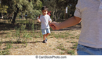 Cute two years old boy and his brother four year old running in the empty park. Social distancing, 2020