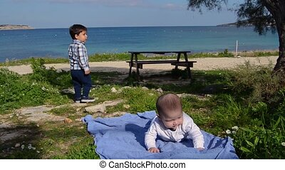 cute two years old boy collecting stones while his baby brother is having tummy timme under the tree