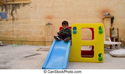 Cute two years old boy dirty from the cookies around the mouth sliding down the plastic slide play house in backyard