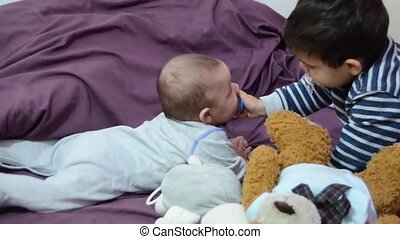 cute two years old boy giving pacifier to his baby brother