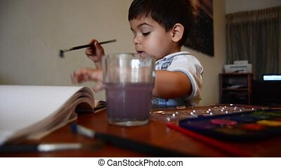cute two years old boy painting with water colours early...