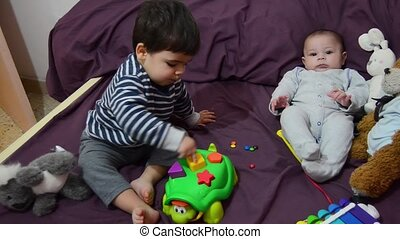 cute two years old boy playing with turtle education toy while his baby brother is watching and smiling