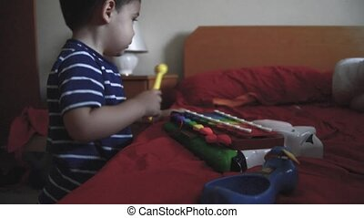 Cute two years old boy playing xylophone in the bedroom.