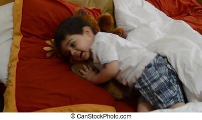 cute two years old boy putting teddy bears in parents bed to...