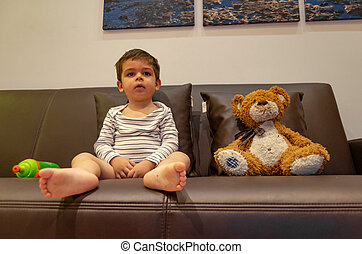 cute two years old boy sitting on the couch with his teddy bear and watching tv