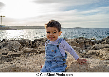 cute two years old boy sitting on the rocks on the sea.