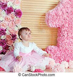 Cute upset baby girl in pink dress