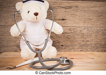 Cute white tebby bear wear nurse with stethoscope and thermometer on wooden background ,vintage tone