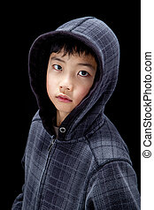 Cute Wide-Eyed Asian Boy in Hoodie Isolated on Black