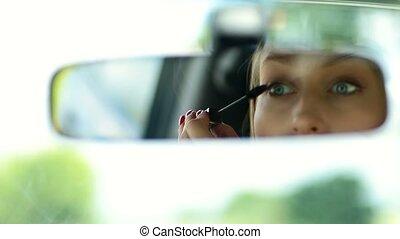 Cute woman applying mascara in car rearview mirror