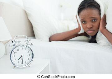 Cute woman being awakened by her alarm clock