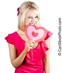 Cute woman biting big red love heart