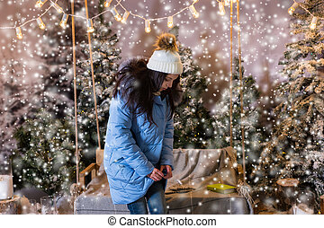 Cute woman buttoned up her blue down jacket and standing near swing with a blanket under the flashlights in a snow-covered park
