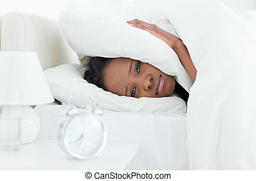 Cute woman covering her ears while her alarm clock is ringing
