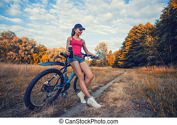 woman cyclist cycling mountain bike in the summer park