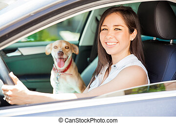 Cute woman driving with her dog